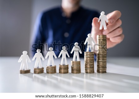 Human Hand Placing Small Human Figure On Increasing Stacked Coins Over Wooden Desk Stock photo ©