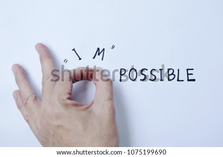 human hand poking impossible to possible words on white paper background