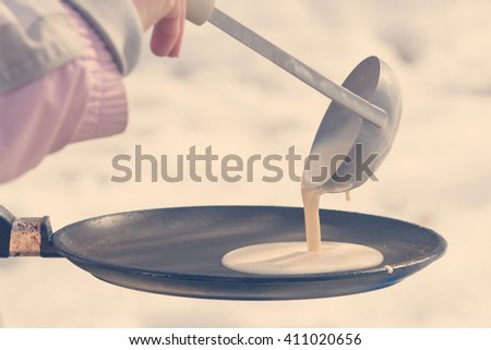 Human hand pouring ladle the batter for pancakes on a frying pan on a background of snow Stock photo ©