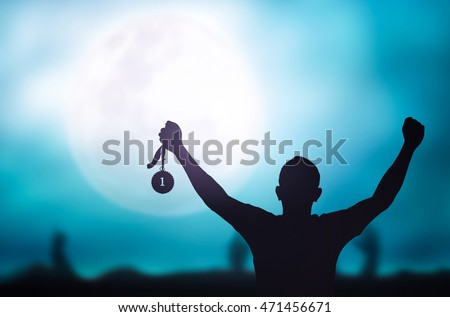 Human hand raised, holding gold medal against sky. Arm Win Goal First Moon Photo Prize Best Match Olympic Hero Metal Cloud Aim Green Blue Day Many Pride Crowd Banner Champ Badge Contest Place Night