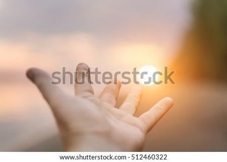 Human hand reaching for the sun #512460322