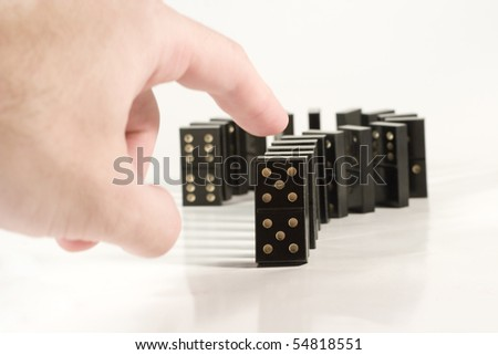Human hand ready to push a row of black dominoes (shallow DOF, focus on the domino piece in front of the row only)