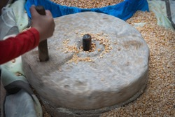 Human hand rotating an ancient stone grinding machine for smashing grains. Handmade manual equipment grind mill