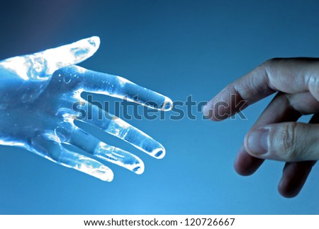 Human hand touch an atrifical glass hand - stock photo