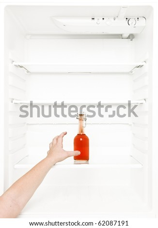 Human hand trying to reach a bottle in the fridge