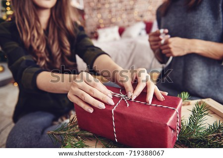 Human hand tying a string on christmas present