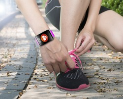 human hand tying shoelaces wearing bright pink watchband touchscreen smartwatch with red health icon on forest trail background