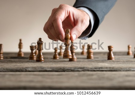 Human hand wearing business suit moving dark King chess piece at table. Conceptual of problem solving.