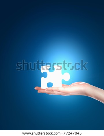 human hand with a blue shining piece of puzzle