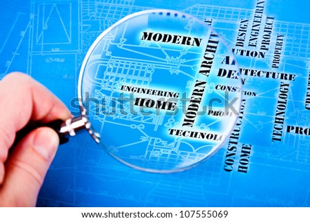 human hand with a magnifying glass on the art architectural background