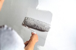 Human hand with large roller of paint begins to paint a white wall handicraft master painter training contrast color sample color test tool renovation gray silver craftsman