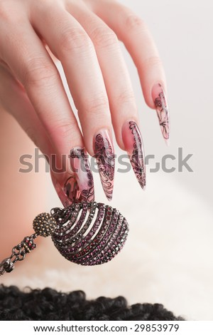 Human hand with long fingernail and beautiful manicure hold beads over gray