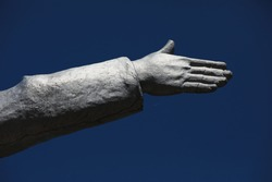 Human hand with palm and fingers extended horizontally indicating the direction.Fragment of a monument covered with silver paint against a blue sky.Part of the sculpture of a man.Isolated close-up