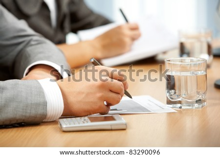 Human hand with pen and document during work at conference