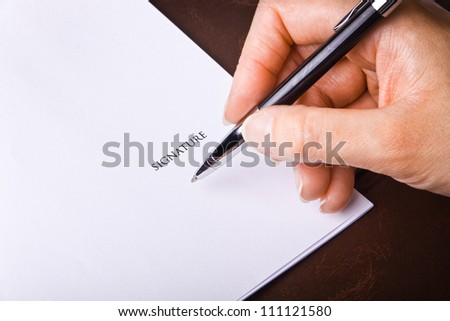 Human hand with pen signing a document