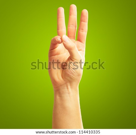 Human Hand With  Two Fingers Pointing Up On Green Background