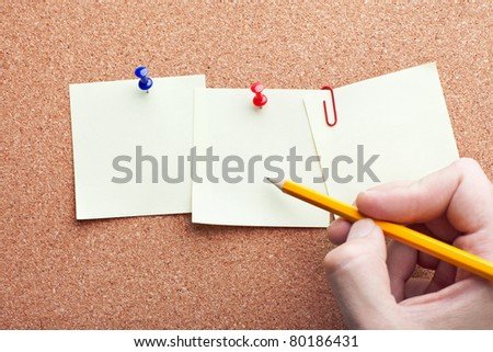 human hand writing with pencil on three note papers on cork board
