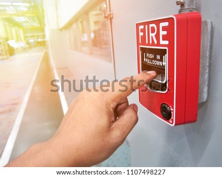 Human hands are pulling fire alarms on the walls along the factory corridor,The concept of a picture about fire alarms in buildings.Soft focus.