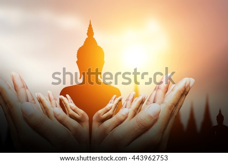 Human hands  bless silhouette of Buddha on sky