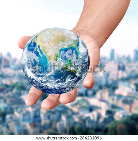 Human hands carrying global Earth over gas clouds and Sun over blurred city a World Environment Day Concept Elements of this image furnished by NASA