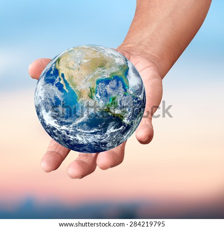 Human hands carrying global Earth over gas clouds and Sun over green glass a World Environment Day Concept Elements of this image furnished by NASA