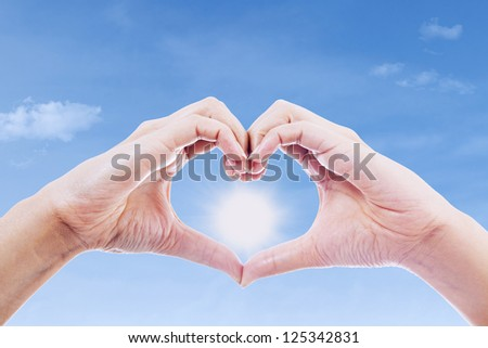 Human hands gesturing a love sign over a sun background - stock photo