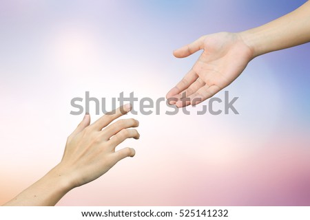 Human hands help together on blur sunset sky backgrounds.faith and belief of religious conceptual:support and kindness of friendship:forgiveness and blessing conception.love/heal/treat of god