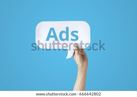 Human hands holding a bubble speech of word 'Ads' in all blue background #666642802