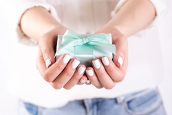 human hands holding a gift. Holiday concept on a light background