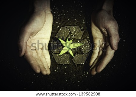 Human hands holding a green sprout and ecology symbols