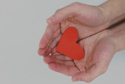 Human hands holding a red heart. Love, kindness, sharing, volunteerism and compassion acts.