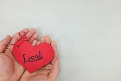 Human hands holding a red heart tag with handwritten word local. Support, promote, buy, shop and love local business concept. Gray background, top view.