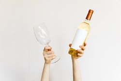 Human hands holding a wine glass and bottle of white wine on wall background.
