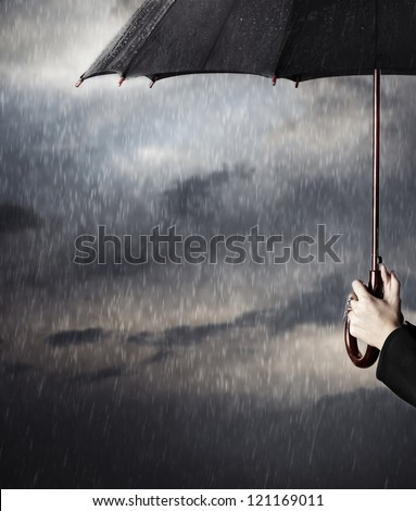 Human hands holding big black umbrella under the heavy rain