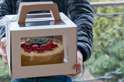 Human hands holding cardboard box with holiday cake decorated of berries. Courier or family member on the front door brings the dessert. Outdoors, copy space, soft selective focus, garden background.