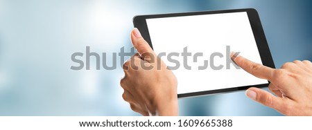 Human hands holding digital tablet with a white blank screen ストックフォト ©