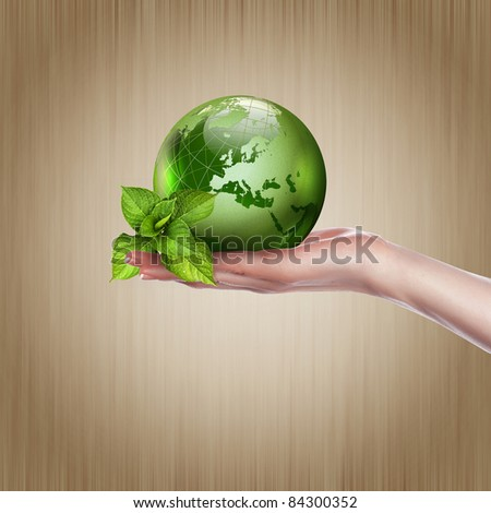 human hands holding green earth with a growing plant
