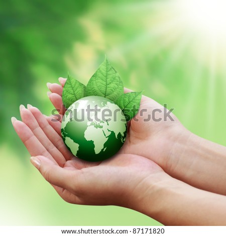 human hands holding green earth with a leaf on nature background - stock photo