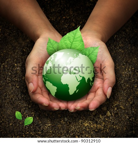 human hands holding green earth with a leaf on soil