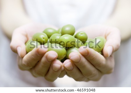 Human hands holding green olive.