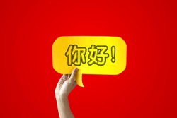 Human Hands Holding 'Nihao' Yellow Speech Bubble Over Red Background - Nihao means Hello in Chinese - Chinese learning concept