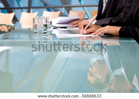 Human hands holding pen and making notes during conference