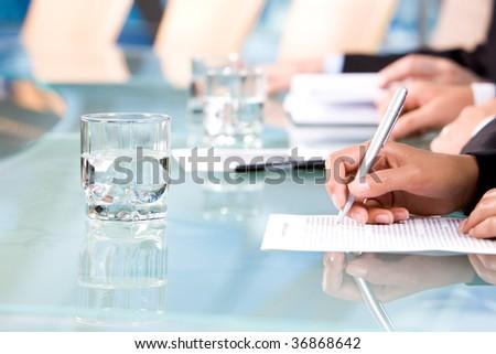 Human hands holding pen and writing report at seminar