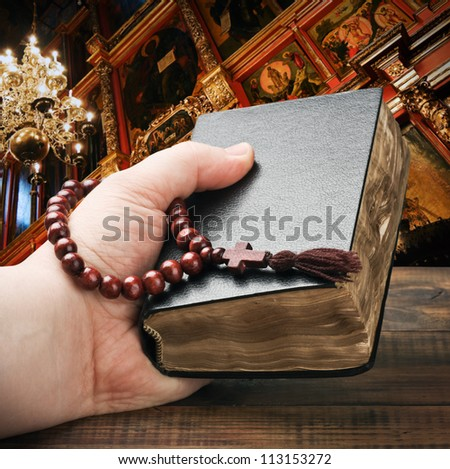 human hands holding the Bible and praying with a rosary