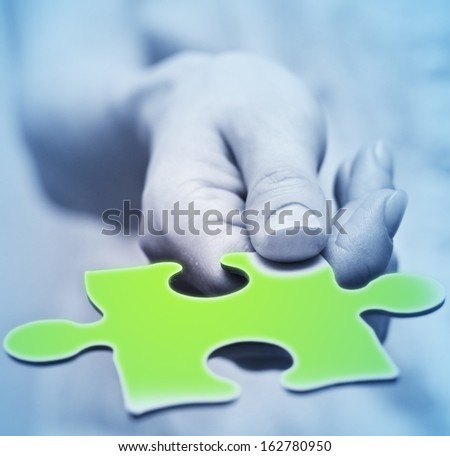 Human hands holding the missing piece .