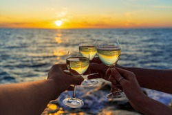 Human hands holding wine glass with sparkling wine against amazing sea landscape at sunset. Friends or family beach party with alcohol drink at sea shore. Summer vacation, weekend at sea concept.