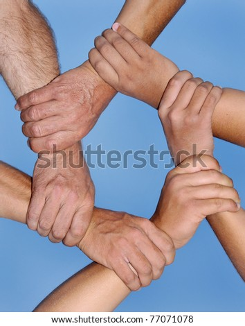 Human hands in a strong link against a deep blue sky