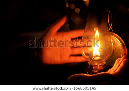 Human hands next to litted oil lamp in a gloom dark night