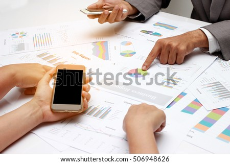 human hands of Group coworkers having discussion during meeting, business people discussing the charts and graphs showing the results of their successful teamwork.