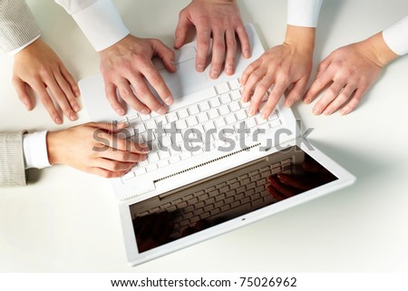 Human hands on keypad of laptop at workplace